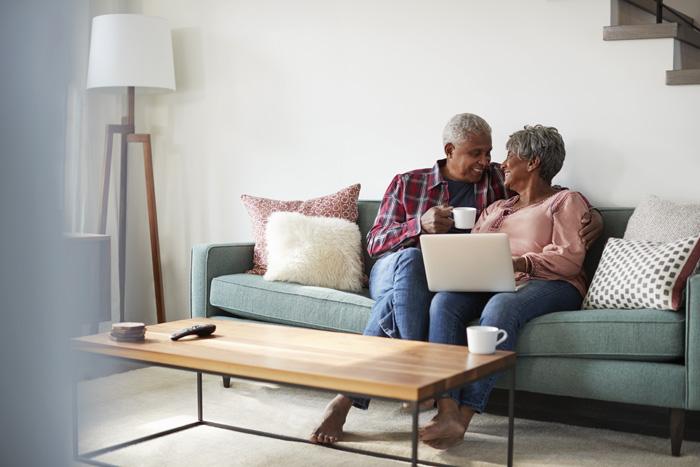 Senior couple on sofa using laptop