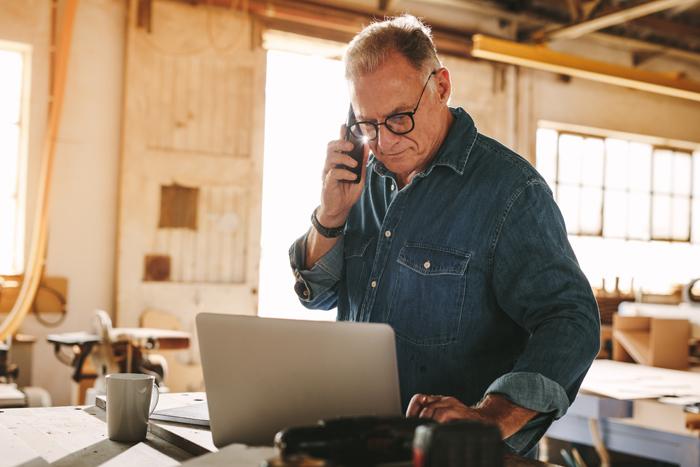 Man on laptop in wood shop